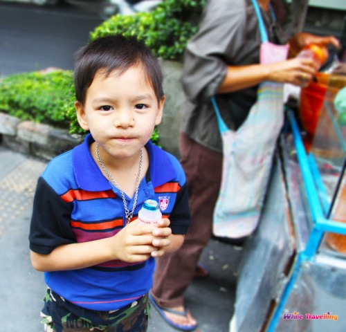 The little kid helpi,ng his dad to seel street food in Bangkok